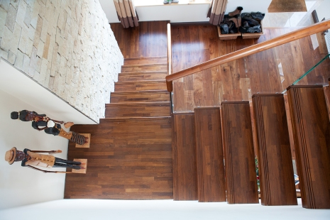 Walnut treads with triple groove design, circular handrail and glass balustrade