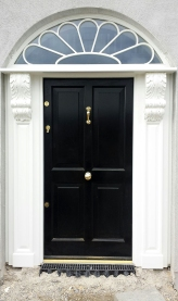 Four panel front entrance door with hand carved columns and arched fanlight